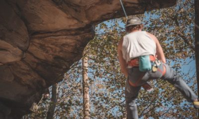man in white tank top and blue denim jeans climbing on brown | Stay Safe: Why You Should Bother With Rock Climbing Insurance | Featured
