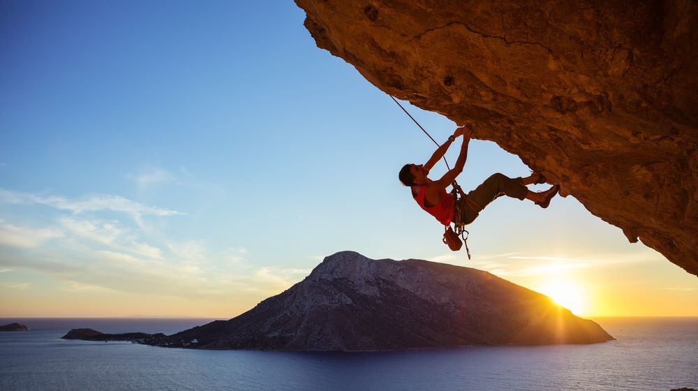 male-climber-on-overhanging-rock-against | 7 Thrilling Rock Climbing Destinations In The U.S. | Featured