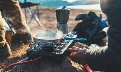 person-cooking-hot-drinks-nature-camping | Best Tent Stoves You Can Bring For Winter Camping | Featured
