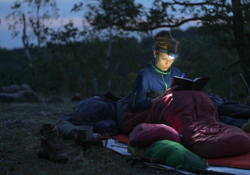 Caucasian female hiker reading book | sleeping bag