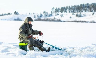young man fishing hole on ice | Ice Fishing Gear for Beginners | Featured